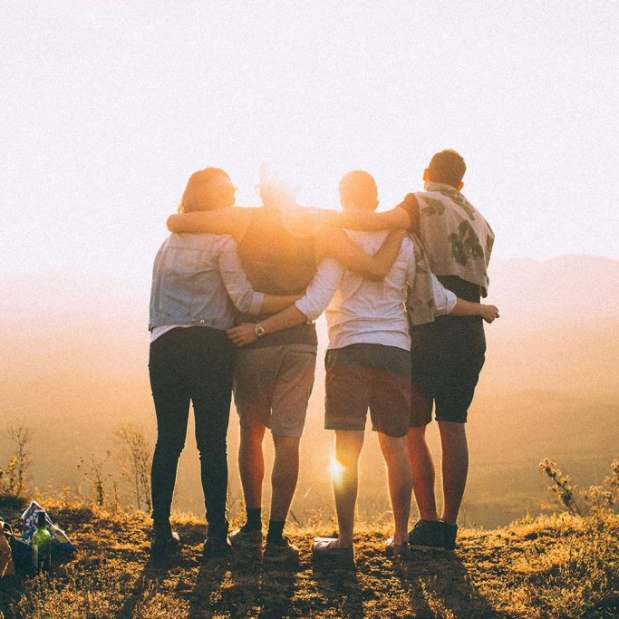 Image of friends hugging over a hill