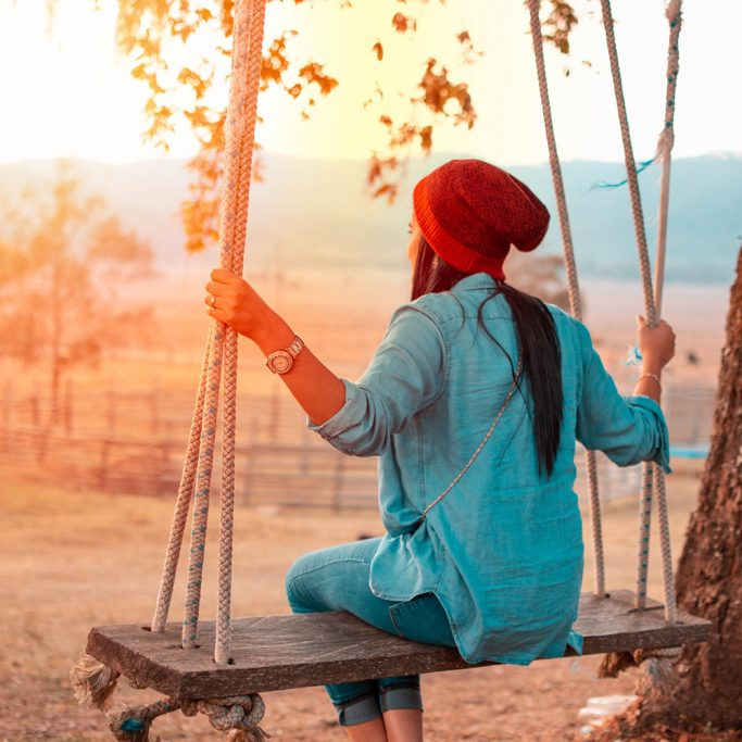 Image of a woman sitting on a swing beside a tree
