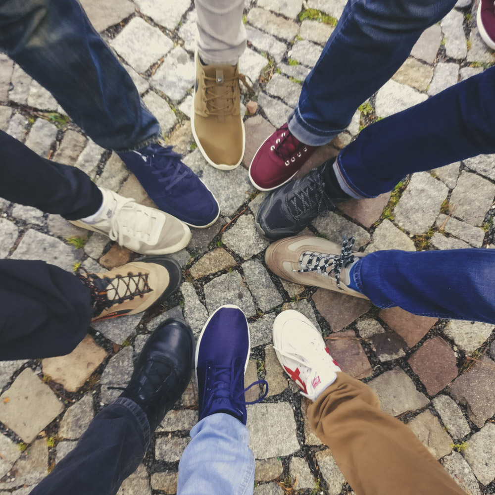 Image looking down at a circle of shoes representing a group