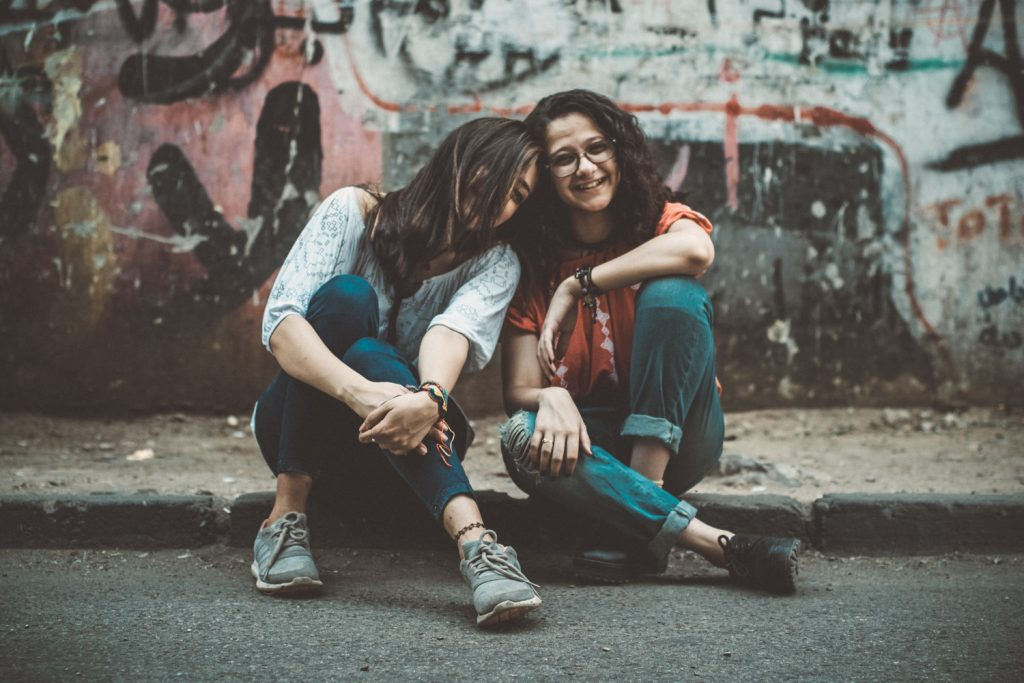 Image of friends sitting on street corner laughing