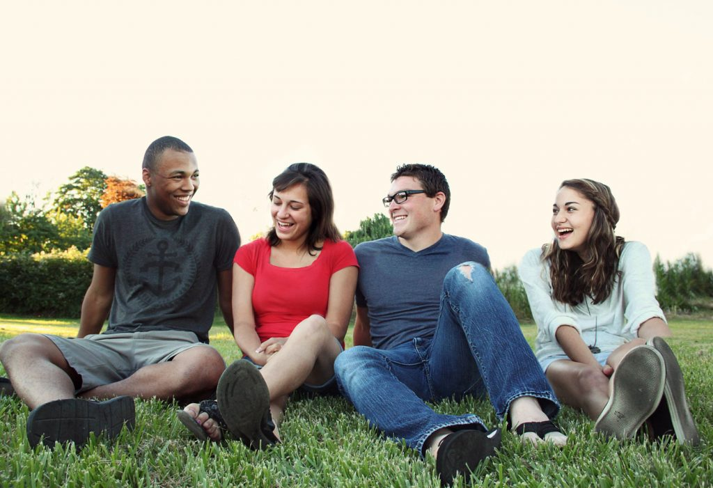 Image of friends sitting in the grass
