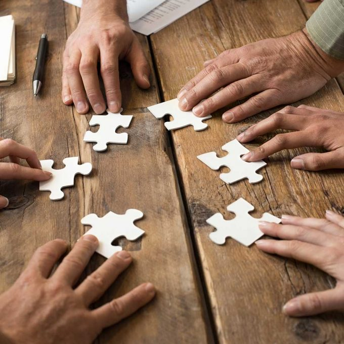 people connecting puzzle pieces together